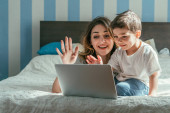 happy mother and toddler boy waving hands while having video call in bedroom