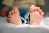 selektivní zaměření bosých nohou roztomilého chlapce na lůžkoviny