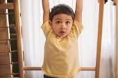 Fényképek aranyos fiú lóg vízszintes rúd közben gyakorló otthoni tornaterem