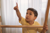 cute boy pointing with finger while touching ladder of home gym