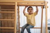 Fényképek imádnivaló fiú gyakorló otthoni tornaterem, miközben ül a létrán