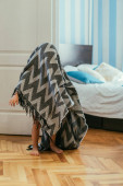 Fotografie kleiner barfüßiger Junge mit Decke bedeckt in der Nähe des Schlafzimmers stehend