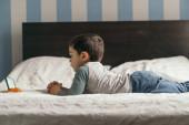 oldalnézetben aranyos fiú feküdt az ágyon, és néz online leckét okostelefon
