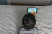 Photo overhead view of kid watching online lesson while lying on bed