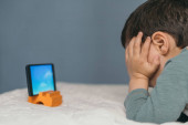 Photo little boy touching head while watching educational cartoon on smartphone while lying on bed