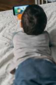 szelektív fókusz a kisfiú néz webinar okostelefon, miközben fekszik az ágyon