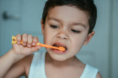cute, concentrated kid brushing teeth in bathroom