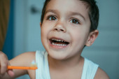 selective focus of cheerful boy holding toothbrush with toothpaste