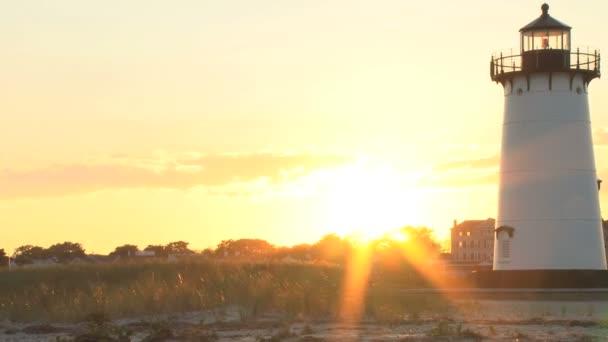 sluneční paprsky splachující majáku a pláže trávy
