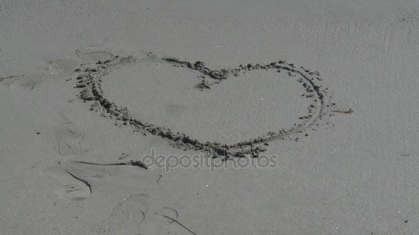 Welle spült Herz im Sand weg