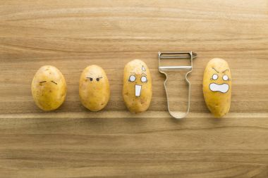 scary face potatoes and peeler on wooden cutting board