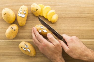 scary face potatoes being cut on a wooden kitchen board