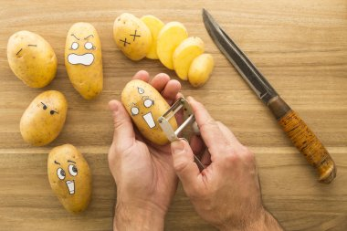 scary face potatoes being peeled on a wooden kitchen board