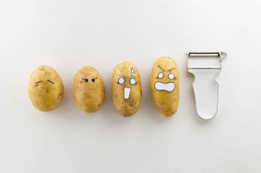 scary face potatoes and peeler on white background