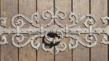 Heavy wooden door with intricate metal ornament