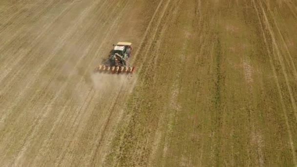 A traktor terepen dolgozik. Traktor vetőgéppel, vetés a mezőn. Mezőgazdasági termények vetése. Traktor egy vetőgéppel, hogy egy hatalmas mezőre vessen. Mezőgazdasági munka. Tavaszi vetés