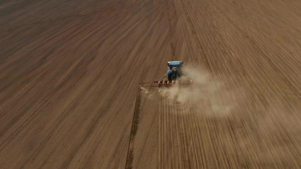 Letecký kinematografický snímek energeticky nasyceného traktoru s půdou obdělávající setou jednotkou produkující obdělávání chudé vyprahlé zemědělské půdy. Obrovské mraky písku a prachu. Boční pohled zepředu