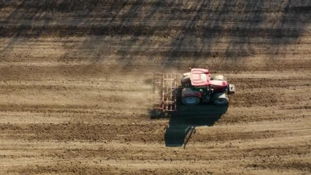 Traktor termőföld és vetés száraz területen. A vetés előtti tevékenységek részeként vetésforgóval rendelkező földterület előkészítése a kora tavaszi időszakban.