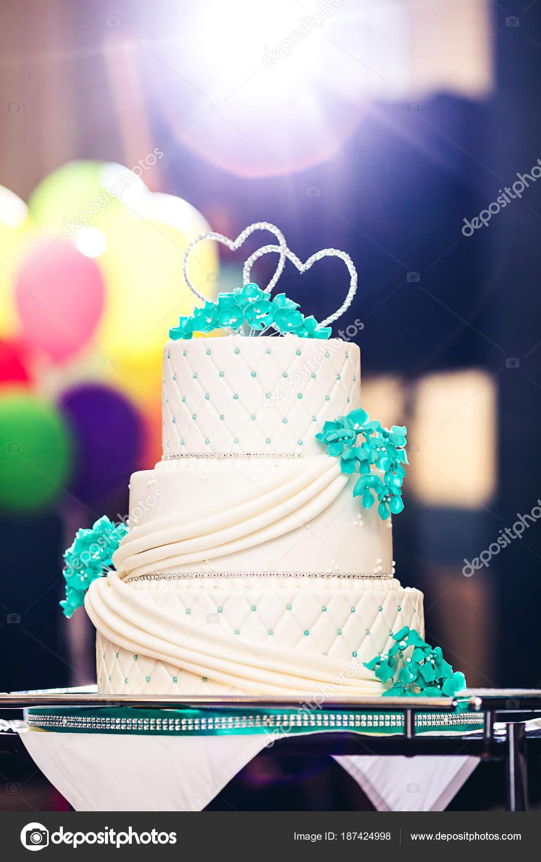 Una bella torta nuziale decorata con fiori blu, strass e cuori.  Retroilluminazione \u2014 Foto