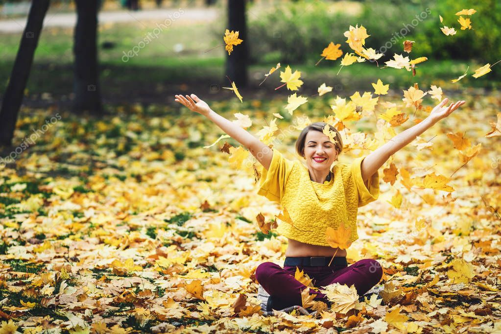 girl in autumn sits on grass and cheerfully casts up yellow leaves. Life style.