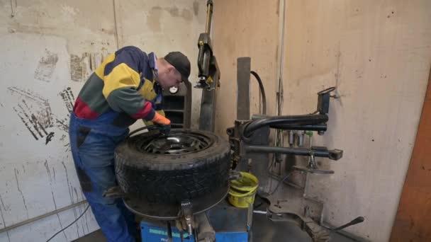 technikus munkás felfújja a gumiabroncsot a garázsban