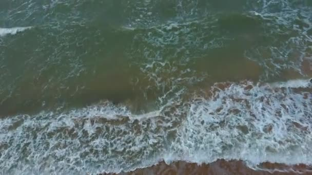 Luftaufnahme mit einer Drohne von der Ostseeküste mit Wellenblick von oben. Meereswellen über einem Sandstrand. Blick von oben auf schäumende und plätschernde Meereswellen, große Wellen von oben