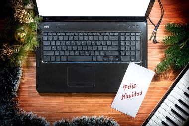 Feliz Navidad - Musical Christmas background with musical keyboard, laptop, laptop, copy space on a wooden table