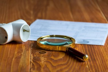 Electricity Bill on a wooden table with magnifier and Electric Splitter