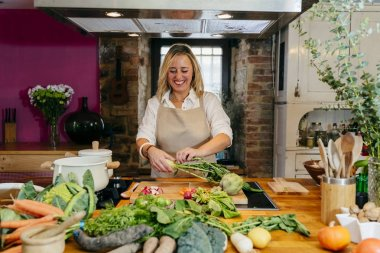 Portrait of smiling blonde woman tearing radish leaves over kitchen table with various vegetables and kitchenware