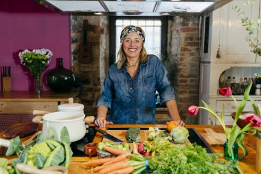Portrait of smiling mature woman posing at kitchen table with vegetables and looking at camera