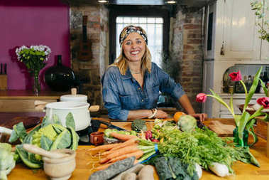 Portrait of smiling mature woman leaning on kitchen table with vegetables and looking at camera