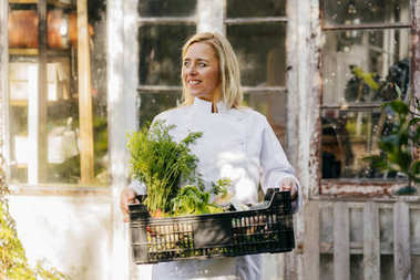 Portrait of smiling blonde woman posing with crates of fresh harvested vegetables and looking away