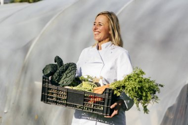Portrait of smiling blonde woman posing with crates of fresh harvested vegetables on backdrop of greenhouse