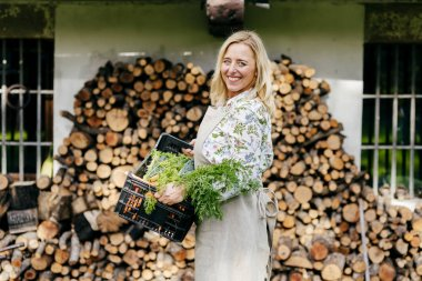 Portrait of smiling blond woman holding crate with harvested vegetables and posing over stack of fire logs