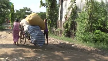 Mandalay, girls with garbage bags on bicycle