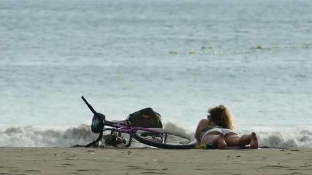 woman with bicycle laying on beach