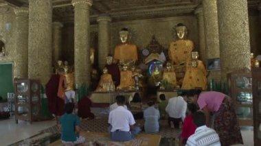People praying to Buddha statues