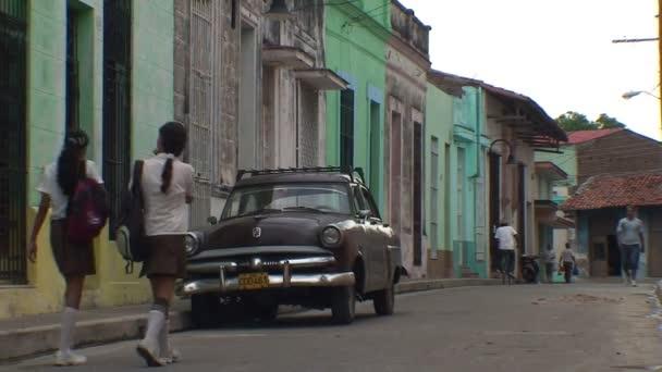 Colonial buildings and retro car