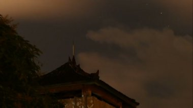 Stars and clouds above temple roof in Indonesia, time lapse