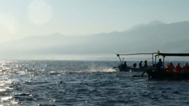 Traditional fishing boats on Bali Sea are waiting for dolphins