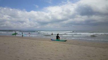 Wave surfers at the sea of Kuta beach, Bali