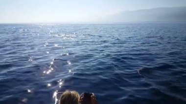 Blond european woman take mobile photos from dolphins in front of boat