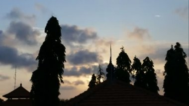 Sunset time lapse above temple roof in Indonesia