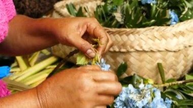 Balinese women hands make sacrificial baskets, Bali