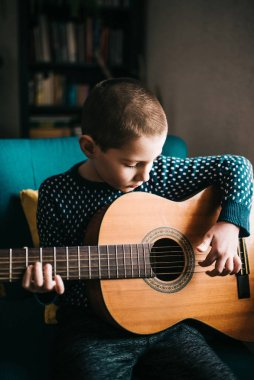 Portrait of little boy playing acoustic guitar at home