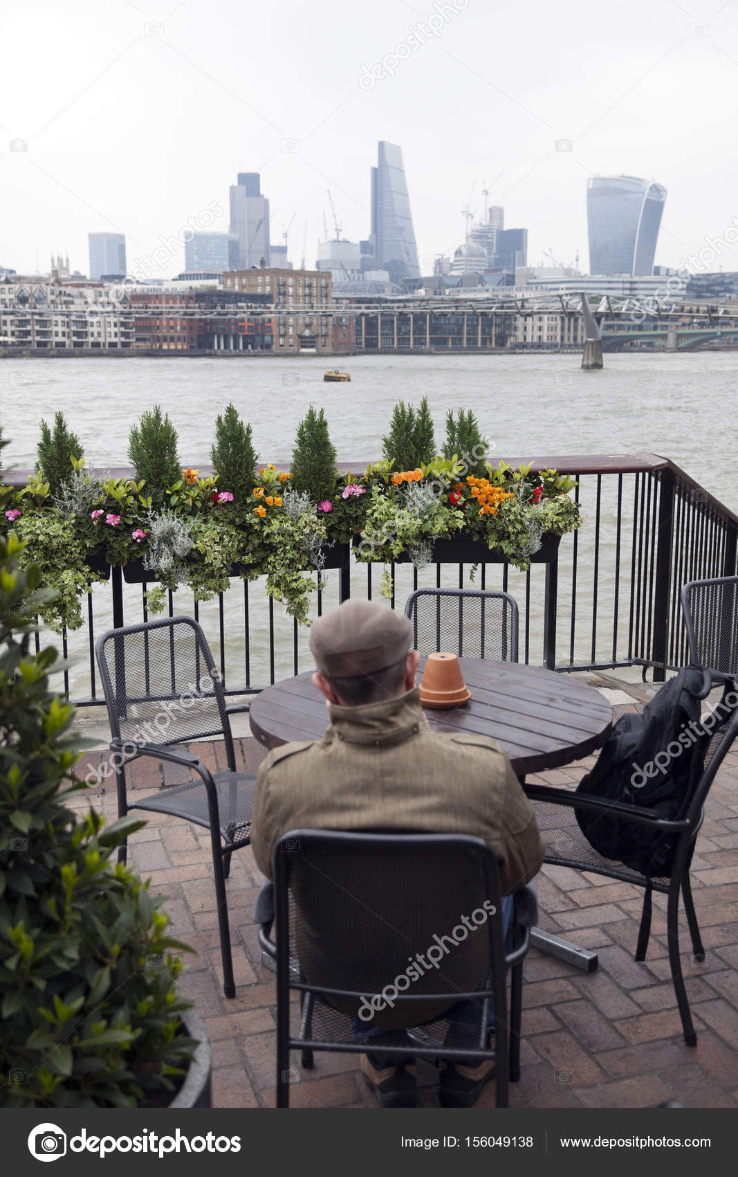 Man Sits At Outdoor Cafe Table With Potted Flowers And Looks Ove U2014 Stock  Photo