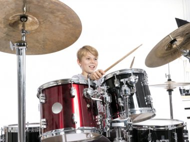 Young teen boy plays the drums in studio against white backgroun