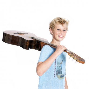 Blond teen boy with guitar in studio against white background