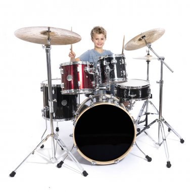 Young caucasian boy plays drums in studio against white backgrou