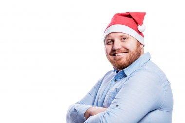 Smiling redhead man in santa claus hat. New Year and Christmas celebration. Isolated on a white background. Space for text.